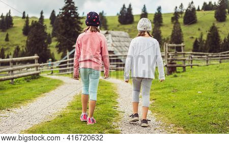 Children Hiking In Mountains Or Meadows With Sport Hiking Shoes.
