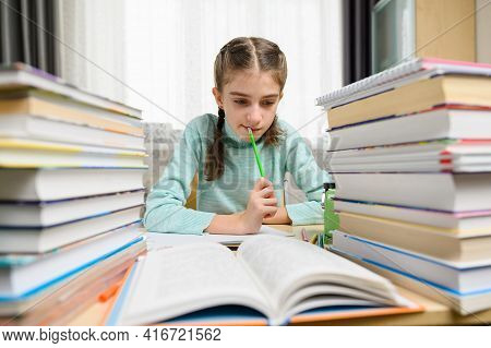 The Girl Looks Thoughtfully At The Textbook While Doing Her Homework. School Girl Doing Homework At
