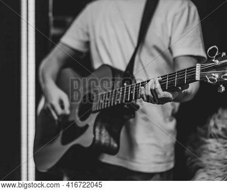 A Man Plays An Acoustic Guitar In A Dark Room. Live Performance, Acoustic Concert, Practice.
