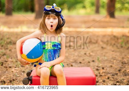 Little Child Girl With Shocked Face Wear Swimsuit With Ball Sitting In Autumn Forest In Swimming Mas