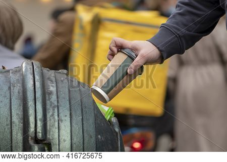 A Man\'s Hand Throws A Paper Coffee Cup Into A Street Trash Can, Close-up, Selective Focus. Concept: