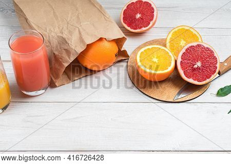 Sliced Citrus Fruits And Citrus Juices On A Wooden Table, Orange And Grapefruit.