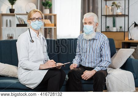 Front View Shot Of Young Woman Nurse Doctor In Mask, Consulting Senior Gray Haired Woman During Home