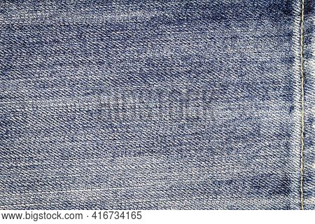 Light Blue Jeans Texture. Denim Fabric Background With A Seam.