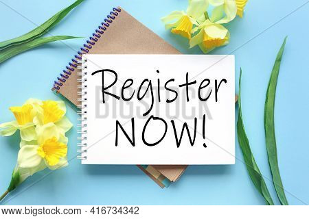 Register Now. Text On White Notepad Paper On Blue Background. Near Notepad With Yellow Flowers And G