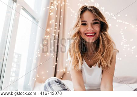 Stunning Fair-haired Woman Expressing Positive Emotions While Posing In Her Light Room. Beautiful Gi