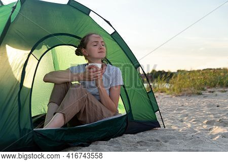 Female Tourist Sitting In Touristic Tent With Cup Of Hot Tea On Sandy Beach. Camping.