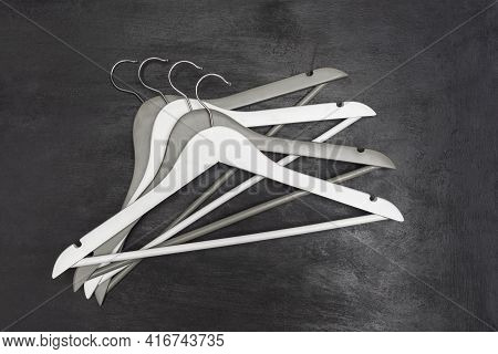 Several Wooden Hangers On Black Background. Top View. Wardrobe Concept.