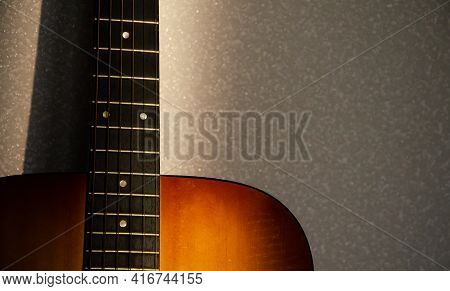 Selective Focus Guitar Fretboard With Strings In Sunbeam On Blurred Gray Background. Music Concept.