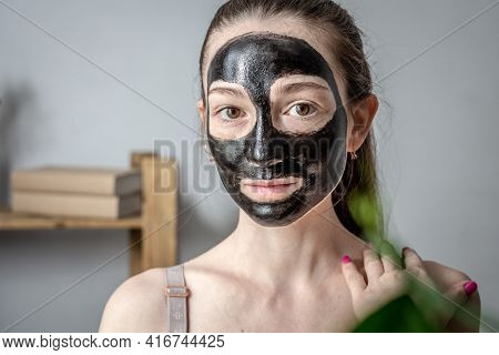 Portrait Of A Young Woman With A Cosmetic Black Mask On Her Face. Concept Of Cosmetic Procedures, Sk