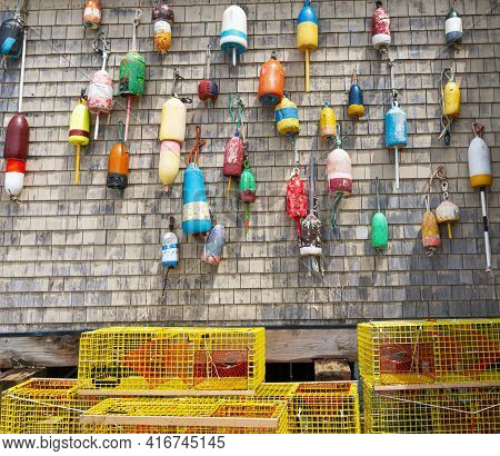 Traditional Vintage Lobster Buoys Hanging On The Wall Of A Building With Yellow Lobster Pots On The