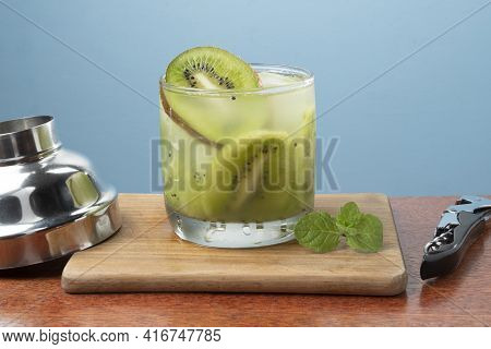 Alcoholic Drink Caipirinha Based On Kiwi And Aguardente Distilled Cocktail Drink And Fruits On Blue