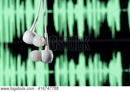 Earphone Hanging With Sound Waves On Blurred Background