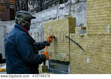 A Man Installs A Layer Of Thermal Insulation On The Wall Of The Stairs Outside - Using Mineral Wool