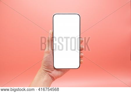 Hand Woman Holding Mobile Smartphone With Blank Screen Isolated On Pink Background, Close-up Hand To