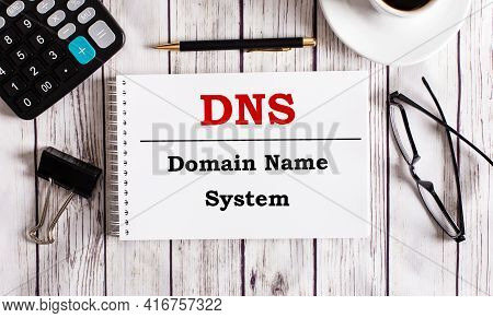 Dns Domain Name System Is Written In A White Notepad Near A Calculator, Coffee, Glasses And A Pen. B