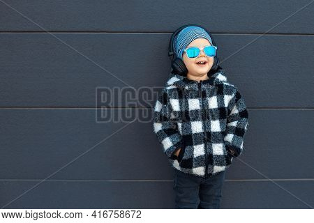 Adorable Fun Child Listen To Music Playing In Earphones On Dark Blue Wall Background. Little Boy Wea