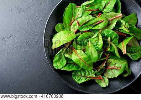 Fresh Swiss Chard Leaves Or Mangold In Black Ceramic Dish On Dark Concrete Background. Concept For T