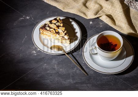 Still Life - Layered Homemade Sponge Cake And A Cup Of Black Tea In A White Dish, And A Linen Napkin