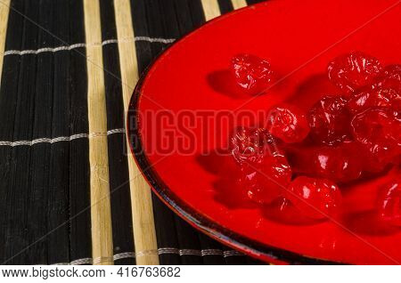 Sweet Dried Cherries In A Red Saucer On A Bamboo Mat, Close-up.