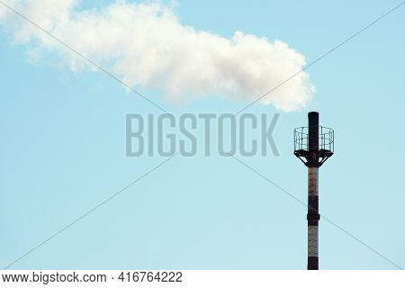 Smoke Is Coming From The Gas Boiler Room Pipe Against The Blue Sky. The Problem Of Environmental Pol
