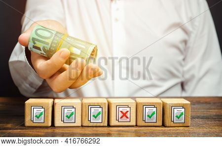 Man Holds Euro Money Above Of Blocks With Permits Documents. Bribe To Obtain Missing Permits. Contra