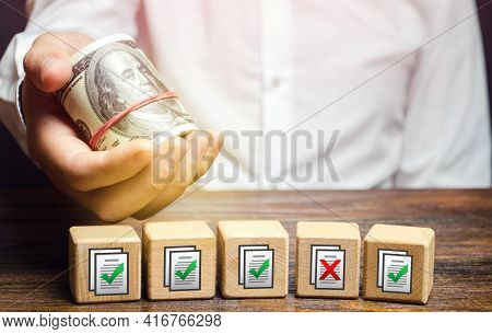 Man Holds Money Above Of Blocks With Permits Documents. Artificial Bureaucratic Obstacles, Corruptio