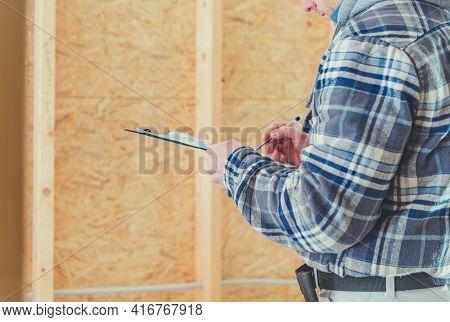 Caucasian Construction Supervisor Making On Site All Necessary Documentation.