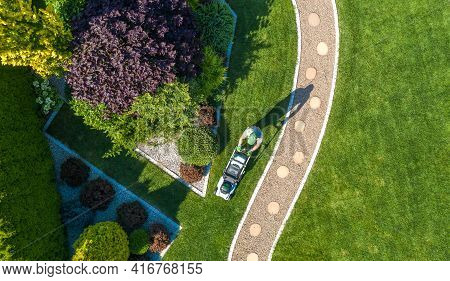 Landscaping Job Grass Mowing Aerial View. Caucasian Gardener With Grass Mower Inside Large Beautiful