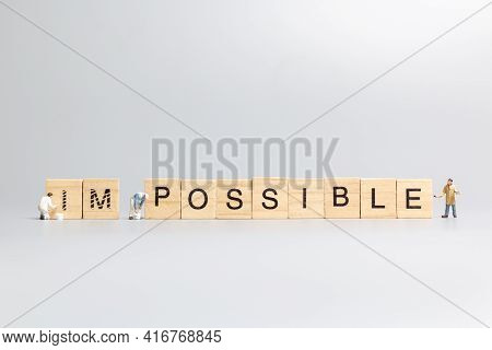 Miniature  People Worker Team On Impossible Word In Wooden Alphabet Letters