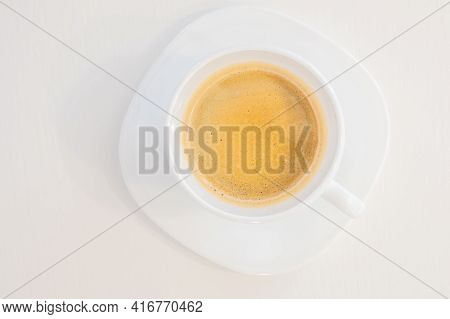 Close up top view of a white cup of coffee isolated on white background