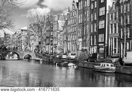 Amsterdam, Netherlands - February 24, 2017: Black And White Amsterdam Canal View, Ordinary People Wa
