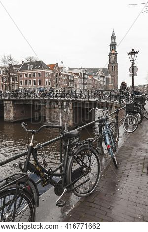 Amsterdam, Netherlands - February 24, 2017: Bicycles Stand Parked Near Canal Coast In Amsterdam Old