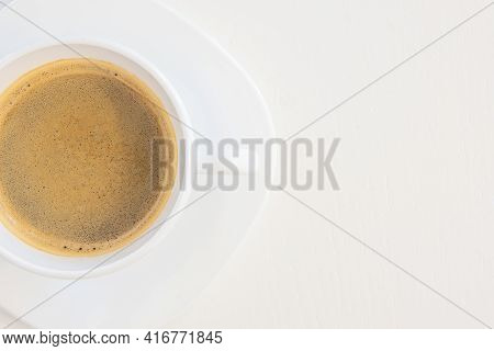 Close up top view of a white cup of coffee isolated on white background with copy space