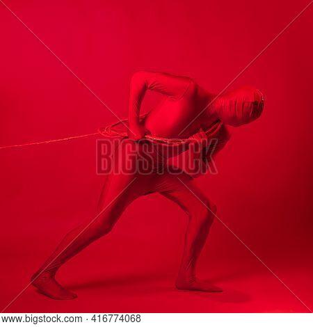 An Anxious Red Man In A Red Leotard, Dragging A Heavy Burden,