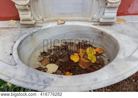 Old Autumn Leaves Lie In Water In Outdoor Marble Wash Basin. Sadness And Discouragement Background