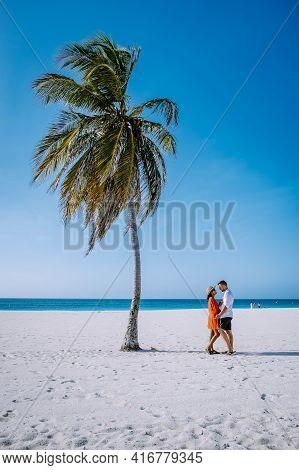 Eagle Beach Aruba, Palm Trees On The Shoreline Of Eagle Beach In Aruba, Couple Man, And Woman On The