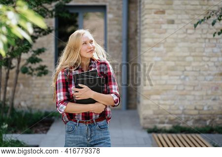 Smiling Young Academy Student Standing Near Campus Building Hugging Copybooks With Faculty Or Lectur