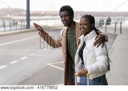 Transfer From Terminal: African Couple Stand Near Airport With Raised Hand Try To Catch Taxi Cab Aft