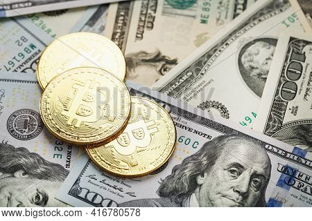 Gold Bitcoin Coins On The Background Of Dollar Bills With The Concept Of The Exchange Rate Of The Fi