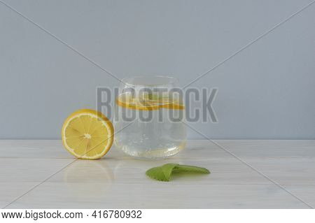 Transparent Glass Of Water, Round Lemon Slice Stand Near And Mint Leaf Lie On Light Grey And Wooden