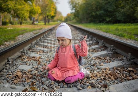Little Girl Sitting On The Railroad Tracks.  Toddler Plays On Railroad In Forest