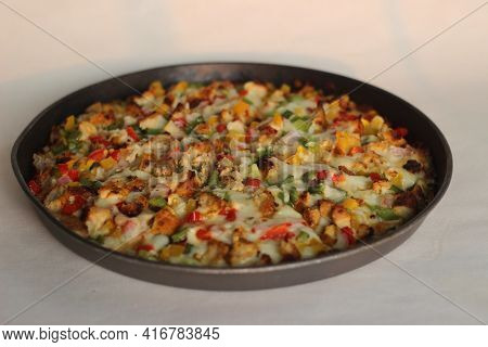A Thin Crust Homemade Pizza Loaded With Cheese, Chicken And Vegetables.