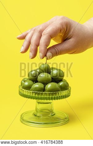 Woman's Hand Grabbing An Olive By The Tail From A Glass Tray Full Of Fresh Green Olives. Stack Of Ol
