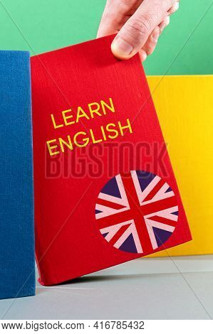 A Man's Hand Holds An English Textbook. Close-up Of Hands And Book. English Language Day Concept.