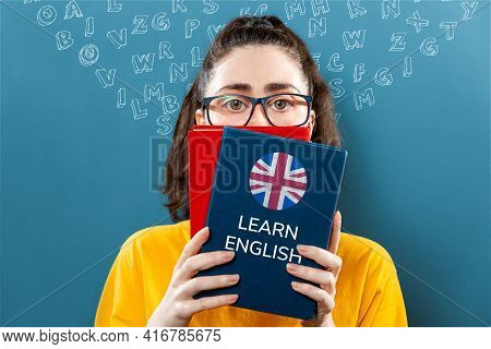 English Language Day. Portrait Of A Young Woman Holding English Dictionary, Covering Half Of Her Fac