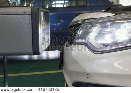 The Device For Adjusting The Light Of The Headlights Stands In Front Of The Left Headlight Of A Whit