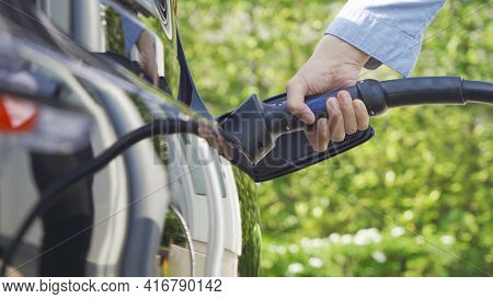 Hand Plugging In Ev Car Charger Or Electric Vehicle. Cable Connect To Gas Station,power Supply Batte