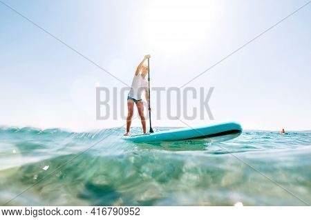 Under The Water View Angle To The Smiling Blonde Teenager Boy Rowing Stand Up Paddle Board. Active F