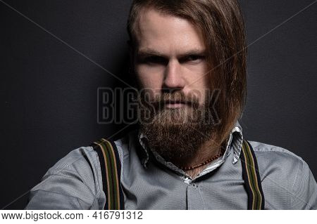Portrait Of A Bearded Man With An Intense Look Standing In A Dark Room Against A Black Background